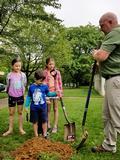 Jim Carpenter invites the children to help shovel dirt around the post.