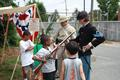 Local children learn about muskets from reenactors.