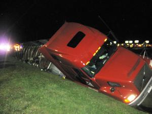 Tractor trailer slides into embankment